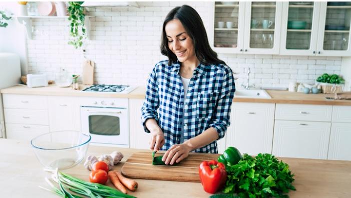 vrouw in keuken bereid maaltijd volgens het eliminatiedieet