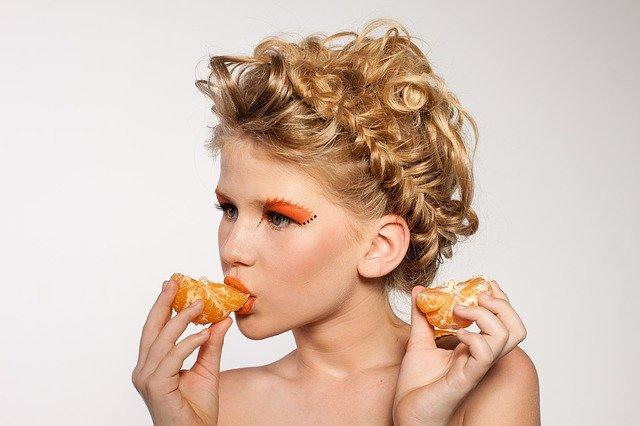 Mooie vrouw die een mandarijn eet